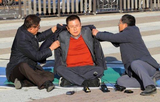 황교안 자유한국당 대표가 20일 오후 청와대 분수대에서 총체적 국정실패 규탄을 위한 단식 투쟁에 들어간 뒤 김문수(왼쪽) 전 경기지사, 차명진 전 의원의 도움을 받아 점퍼를 입고 있다./사진=뉴시스