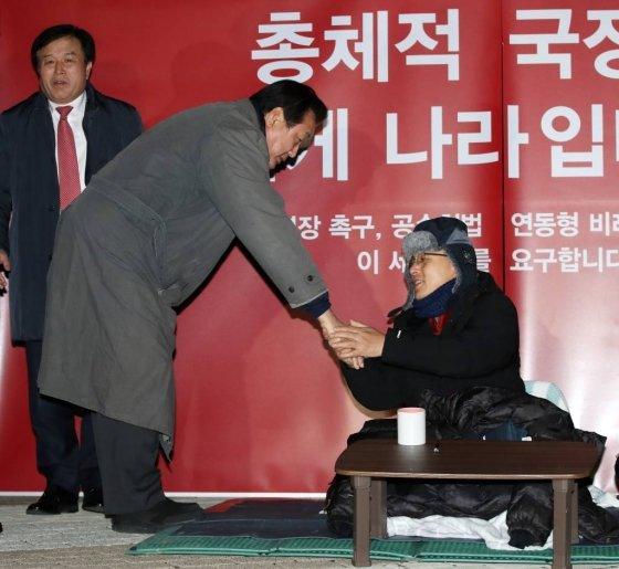 김무성 자유한국당 의원이 21일 오후 서울 청와대 분수대 앞에서 총체적 국정실패 규탄을 위한 단식 투쟁을 하고 있는 황교안 자유한국당 대표를 찾아 악수하고 있다./사진-뉴시스