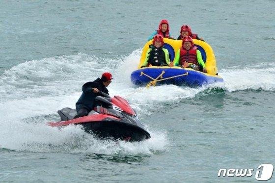 지난 7월 경북 포항시 남구 구룡포해수욕장을 찾은 피서객들이 안전모를 착용하고 레저기구를 타며 더위를 식히고 있다. /사진=뉴스1