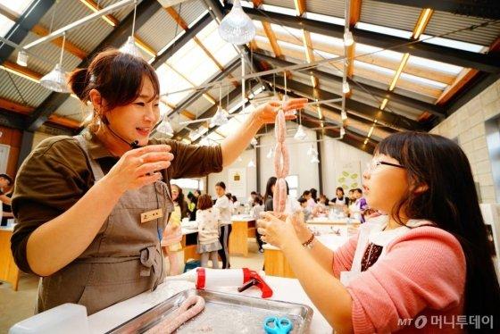 상하농원을 찾은 한 학생 참가자가 직접 소세지를 만들며 즐거워 하고 있다./사진제공=상하농원
