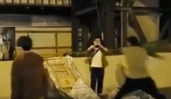 한 시위대가 하수구 덮개로 청소하는 시민을 내리치고 있다. - SCMP 갈무리