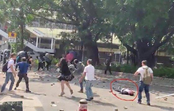 홍콩 시위대가 과격 시위를 말리는 주민에게 벽돌을 던져 70세 주민이 의식불명 상태에 빠졌다. 빨간 원은 길거리에 쓰러져 있는 주민 - SCMP 갈무리