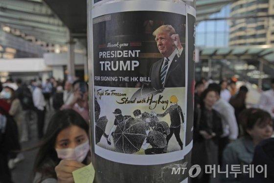 """[홍콩=AP/뉴시스]28일(현지시간) 홍콩 시위대가 시내 금융가에서 시위를 벌이며 도널드 트럼프 미국 대통령의 홍콩 인권법 서명에 고마움을 표하는 포스터를 기둥에 붙이고 있다. 중국 정부는 트럼프 대통령이 홍콩 인권법에 서명한 것에 관해 '중대한 내정간섭'이라고 맹비난했다. 중국 외교부는 이날 성명을 내고 """"미국이 고집대로만 한다면 중국도 반드시 반격 조치를 취할 것이며 그에 따른 책임은 모두 미국이 져야 할 것""""이라고 경고했다. 2019.11.28."""