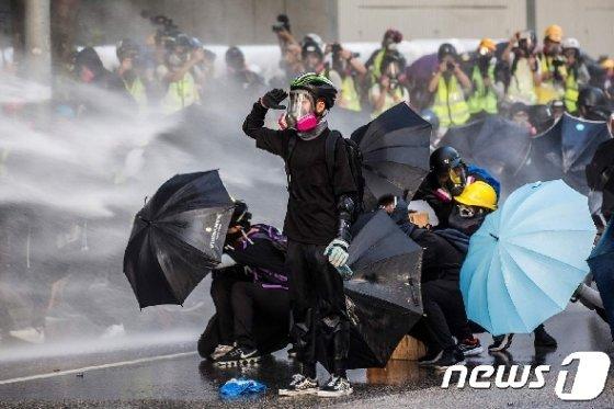 지난 9월15일 홍콩 정부청사 밖에서 열린 반정부 집회에서 시위대가 경찰이 뿌리는 물대포에 우산으로 맞서고 있다. © AFP=뉴스1