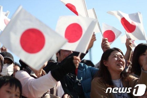 지난달 10일 일본 국기를 흔들며 일왕 행차를 환영하고 있는 일본 시민들.  © AFP=뉴스1