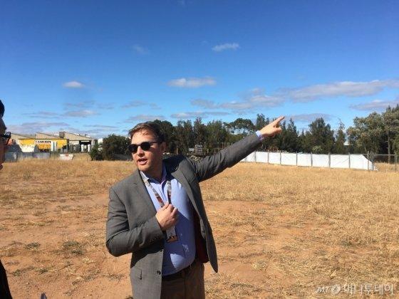 오웬 샤프 남호주정부 개발담당관이 기자에게 6월 완공될 수소파크 현장을 소개하고 있다. 멀리 보이는 공장 지붕에 설치한 태양광판을 통해 수소파크에서 하루 500kg의 수소를 생산한다는 계획이지만, 아직 부지는 허허벌판이다./사진=우경희 기자