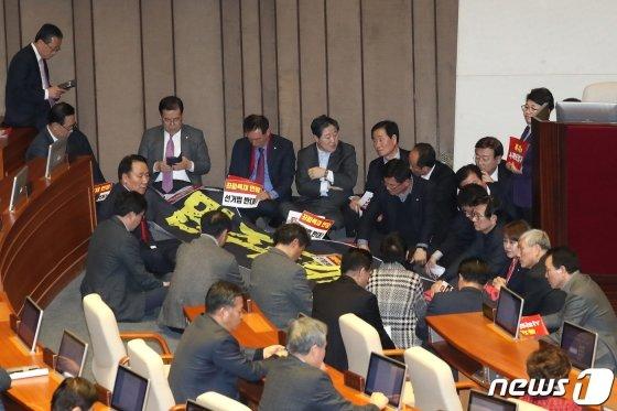 <br>(서울=뉴스1) 임세영 기자 = 자유한국당 의원들이 27일 서울 여의도 국회 본회의장에서 제373회 국회(임시회) 제1차 본회의 개의를 막기위해 의장석을 둘러싸고 있다. 이날 국회에서는 선거법이 표결에 붙여질 예정이다. 2019.12.27/뉴스1 <저작권자 © 뉴스1코리아, 무단전재 및 재배포 금지>