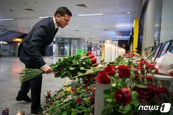 볼로디미르 젤렌스키 우크라이나 대통령이 9일(현지시간) 키예프 외곽 보리스필 국제공항에 마련된 우크라이나 항공 여객기 추락사고 사망 승무원들의 빈소를 방문해 헌화를 하고 있다. © AFP=뉴스1 © News1 우동명 기자