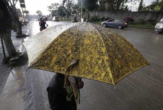 필리핀 타가이타이에서 12일 인근 탈 화산이 분출하면서 화산재가 쏟아지자 한 주민이 우산을 받쳐들고 걸어가고 있다./사진=뉴스1