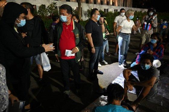 필리핀 현지 공무원이 12일(현지시간) 마닐라 화산재가 공기 중에 퍼지면서 화산재를 방지하기 위한 마스크를 배포하면서 노숙자들과 대화를 나누고 있다./AFPBBNews=뉴스1