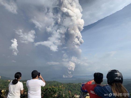 12일 (현지시간) 필리핀 마닐라 인근 관광 명소인 카비테주 타가이타이에 위치한 탈 화산이 폭발해 화산재가 솟아오르고 있다. 이날 화산 폭발로 주민과 관광객 최소 6000여 명이 대피하고 마닐라 국제공항의 항공기 운항이 전면 중단됐다. /AFPBBNews=뉴스1