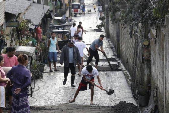 12일(이하 현지시간) 필리핀 수도 마닐라 남부 카비테주 타가이타이의 탈(Taal) 화산이 폭발해 13일 인근 주민들이 동네에 쌓인 화산재를 치우고 있다. /사진=뉴시스