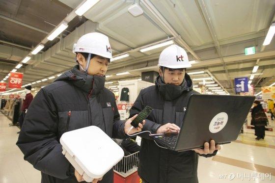 KT 네트워크부문 직원들이 경기도 안양시 홈플러스 매장 내에 고성능 광중계기를 설치하고 5G 서비스 품질을 확인하고 있다./사진=KT