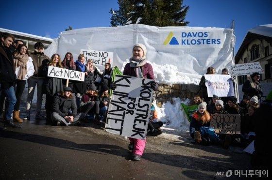 지난해 1월에 열린 다보스 포럼에서 환경운동가 그레타 툰베리가 '기후 변화를 위한 학교 파업' 피켓을 들고 기후 변화 대책을 촉구하고 있다/AFP
