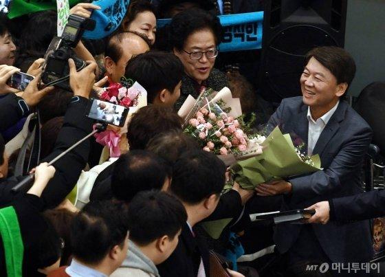 바른미래당 안철수 전 의원이 19일 오후 인천국제공항을 통해 귀국, 지지자들에게 꽃다발을 받고 있다. / 사진=홍봉진 기자 honggga@
