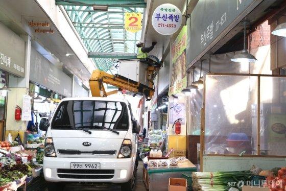 한국전력이 전통시장에서 노후조명설비 교체 작업을 하고 있다./사진제공=한전