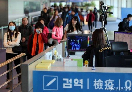 인천국제공항에서 질병관리본부 국립검역소 직원들이 중국발 항공기를 통해 입국하는 승객들의 체온을 측정하고 있다. /사진=이기범 기자.