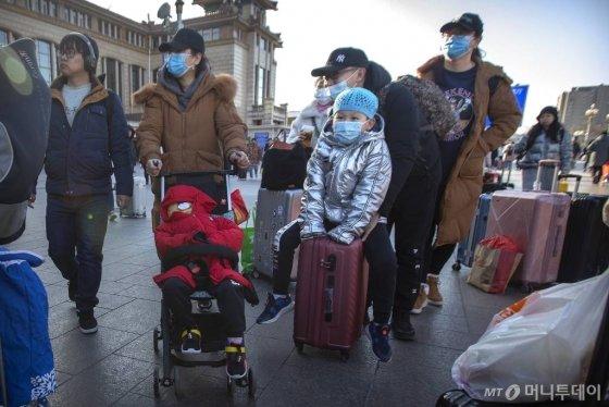[베이징=AP/뉴시스]20일(현지시간) 중국 베이징의 베이징 철도역 앞에 여행객들이 마스크를 쓰고 이동하고 있다. 중국 정부는 우한 폐렴이 수도 베이징에서도 발생하면서 신종 코로나바이러스에 감염된 사람의 수가 급격히 늘고 있다고 발표했다. 특히 연휴를 맞아 수백만 명이 열차와 비행기를 이용하는, 중국에서 가장 인구 이동이 많은 시기와 겹쳐 대규모 확산이 우려되고 있다. 2020.01.20.