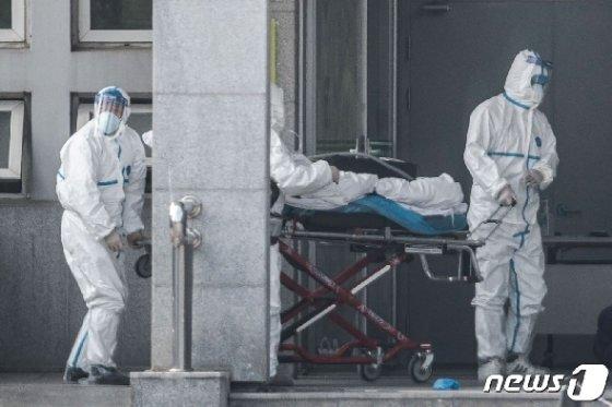 20일(현지시간) 중국 후베이성 우한의 한 병원에서 직원들이 '우한 폐렴' 환자를 옮기고 있다. © AFP=뉴스1 © News1 우동명 기자