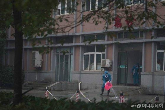 [우한=AP/뉴시스] 신종 코로나바이러스가 원인균으로 알려진 폐렴에 감염된 환자들이 수용돼 있는 중국 우한치료센터(Wuhan Medical Treatment Center)의 22일 외부 모습. 보호복을 입은 사람이 물을 끼얹고 있다. 2020.01.23