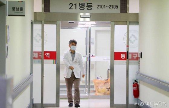 [전주=뉴시스] 김얼 기자= 전북 전주시에서 중국 우한 폐렴의 원인체로 알려진 신종 코로나바이러스 감염증 의심 환자가 발생한 22일 전북대학교 21병동에서 병원 관계자가 의심 환자가 격리 조치된 통제구역에서 빠져나오고 있다. 2020.01.22.  pmkeul@newsis.com