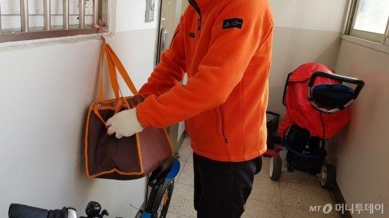 22일 행복도시락 북부센터 직원이 결식아동의 집을 방문해 가방 안에 도시락을 넣고 있다. /사진=김영상 기자