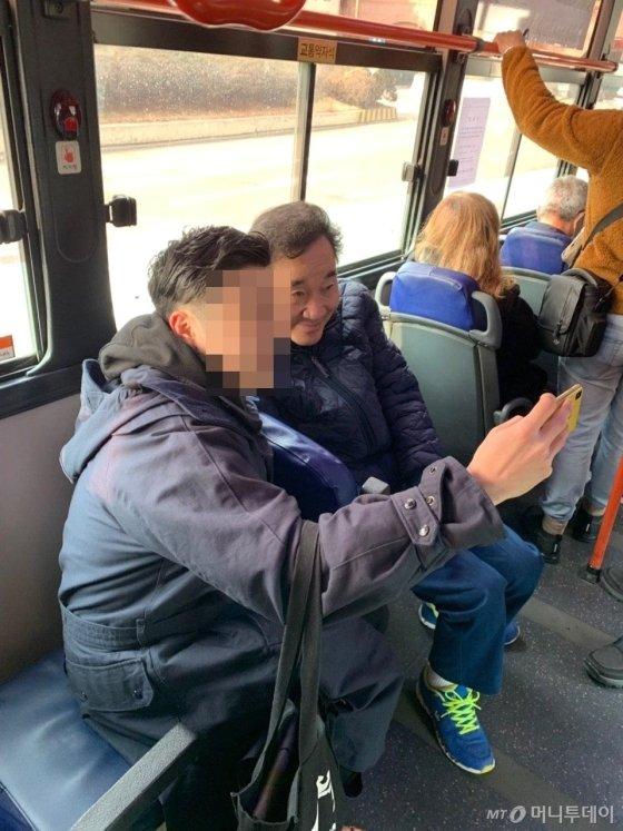 이낙연 전 국무총리가 24일 첫 공식일정을 소화하기 위해 버스를 타고 이동하는 모습. 한 시민의 요청으로 사진을 찍고 있다. / 사진=김하늬 기자