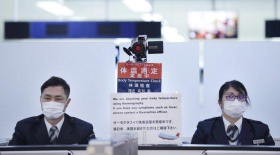 일본 나리타(나리타) 공항 근무자들이 중국 우한(武漢)발 비행기를 타고 입국하는 승객들을 에서 검사하고 있다./사진=AFP