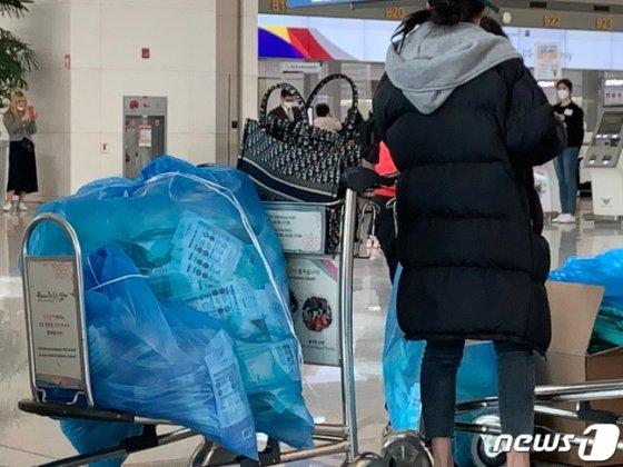 우한폐렴(신종 코로나바이러스 감염증) 확진자가 아시아를 넘어 유럽, 미주 등 전 세계로 확산되고 있는 28일 오후 인천국제공항 출국장에서 중국여행자들이 한국에서 구입한 마스크를 비닐봉투에 가득담아 출국수속을 기다리고 있다. (독자제공) 2020.1.28/뉴스1
