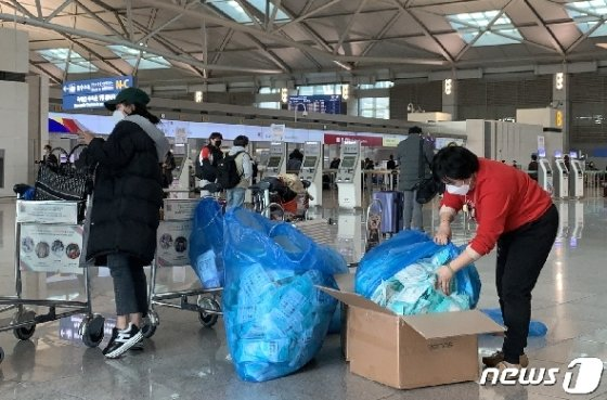 우한폐렴(신종 코로나바이러스 감염증) 확진자가 아시아를 넘어 유럽, 미주 등 전 세계로 확산되고 있는 28일 오후 인천국제공항 출국장에서 중국여행자들이 한국에서 구입한 마스크를 비닐봉투에 옮겨 담고 있다.(독자제공) 2020.1.28/뉴스1