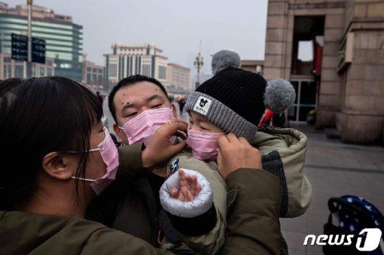 어린 자녀의 마스크를 고쳐주는 중국 우한의 어머니 <자료 사진> © AFP=뉴스1
