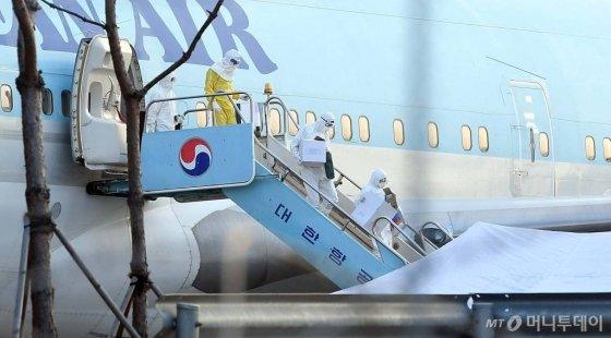 중국 우한 거주 한국 교민 수송에 투입된 전세기가 도착한 31일 서울 강서구 김포국제공항에서 검역관들이 내리고 있다. / 사진=이기범 기자 leekb@