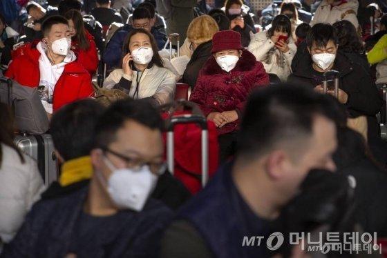 중국 베이징 열차역에서 마스크를 쓰고 열차를 기다리고 있는 승객들