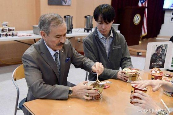 [서울=뉴시스] 박민석 기자 = 해리 해리스(Harry Harris) 주한 미국대사가 10일 서울 종로구 주한 미국대사관에서 대사관 직원들과 '짜장 컵라면'을 먹으며 오스카 시상식을 시청하고 있다. 해리 해리스 대사는 이날 자신의 SNS를 통해 '기생충 으로 한국 영화 최초의 아카데미 각본상을 수상한 봉준호 감독에게 축하를 전한다'는 내용의 글을 업로드했다. (사진=주한 미국대사관 제공) 2020.02.10.  photo@newsis.com