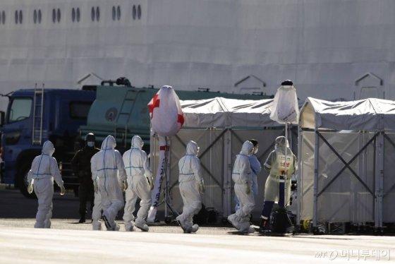 [가나가와=AP/뉴시스]11일 일본가나가와현 내 요코하마항에 정박해 있는 크루즈 다이아몬드 프린세스호로 보호복을 착용한 의료진들이 들어가고 있다. 이 크루즈에서 총 165명의 신종 코로나바이러스 감염증 확진자가 나왔다. 2020.02.11.