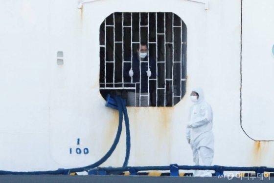 10일 일본 요코하마 항구에 정박 중인 '다이아몬드 프린세스'에서 한 선원(왼쪽)이 보호장비를 갖춘 근로자에게 말을 걸고 있다. 지난달 20일 이곳을 출발했던 이 크루즈선은 중간에 홍콩에서 내린 홍콩인이 신종 코로나 바이러스 확진 판정을 받으면서, 바이러스 확산 우려로 출발지로 돌아온 후에도 승객(승무원 포함) 전원이 내리지 못하고 있다. 약 3700명의 승객 중 확진자는 이날 60명이 늘면서 총 130명이 됐다. / 사진제공=로이터