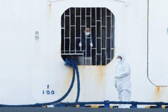 10일 일본 요코하마 항구에 정박 중인 '다이아몬드 프린세스'에서 한 선원(왼쪽)이 보호장비를 갖춘 근로자에게 말을 걸고 있다/사진제공=로이터