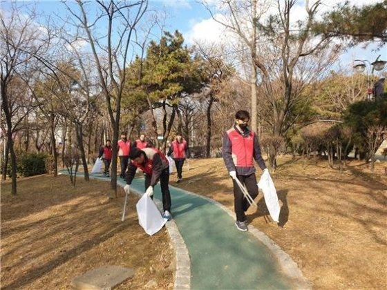 주안 캐슬&더샵 봉사단이 환경정화를 위해 쓰레기를 줍고 있다./사진제공=롯데건설