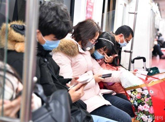 [시안=신화/뉴시스]27일(현지시간) 중국 산시성 시안의 한 지하철 탑승객들이 마스크를 착용한 채 이동하고 있다. 구를 소독하고 있다. 시안시 관계자는 신종 코로나바이러스의 확산을 막기 위해 지하철역, 관광지, 공공 지역 등의 소독 및 검역을 강화했다고 밝혔다. 2020.01.28.