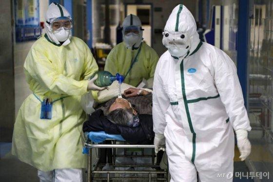 [우한=AP/뉴시스] 중국 후베이성 우한의 한 병원에서 6일 보호복을 입은 의료진이 코로나 19 환자를 격리병동으로 옮기고 있다. 2020.02.13