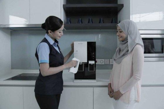코웨이 말레이시아 법인의 제품관리 전문가가 고객에게 정수기 관리법에 대해 설명하고 있다/사진제공=코웨이
