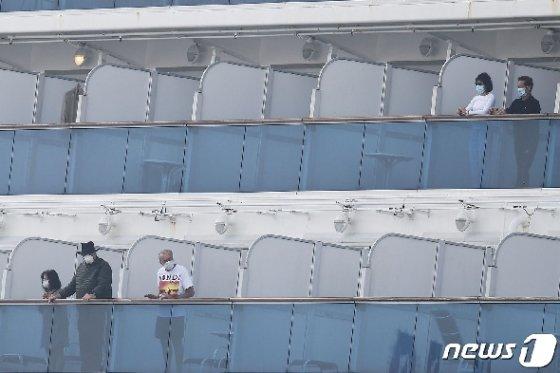 14일 신종 코로나바이러스 감염자 급증 속 요코하마항에 강제 격리된 채 정박해 있는 다이아몬드 프린세스호의 승객들이 마스크를 쓰고 밖을 내다보고 있다. © AFP=뉴스1 © News1 우동명 기자
