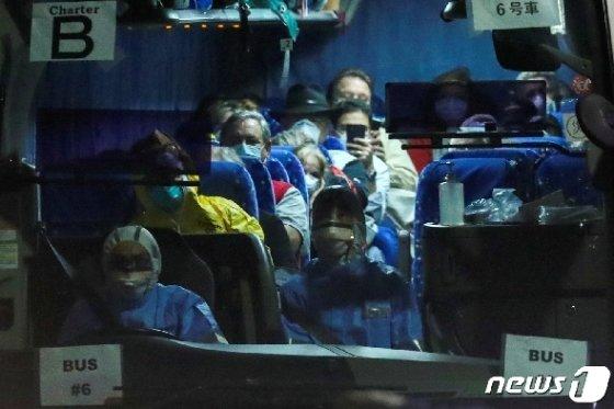 17일 (현지시간) 코로나19 환자가 집단 발생한 요코하마항에 정박 중인 크루즈선 다이아몬드 프린세스호에 탑승했던 미국인이 도쿄 하네다 공항에서 전세기를 타기 위해 버스로 이동을 하고 있다. © 로이터=뉴스1 © News1 우동명 기자