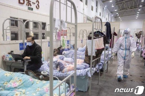 병상에 누워있는 환자들 사이로 노트북을 하는 한 남성환자 모습도 보인다. © AFP=뉴스1
