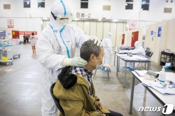 의료진이 중년 환자에게 목 마사지를 해주고 있다. © AFP=뉴스1