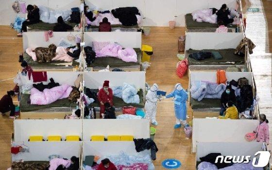 18일 코로나 19의 발원지인 후베이성 우한의 체육관에 설치된 칸막이가 쳐진 임시병원에서 의료진들이 경증환자들을 점검하고 있다. © AFP=뉴스1 © News1 우동명 기자