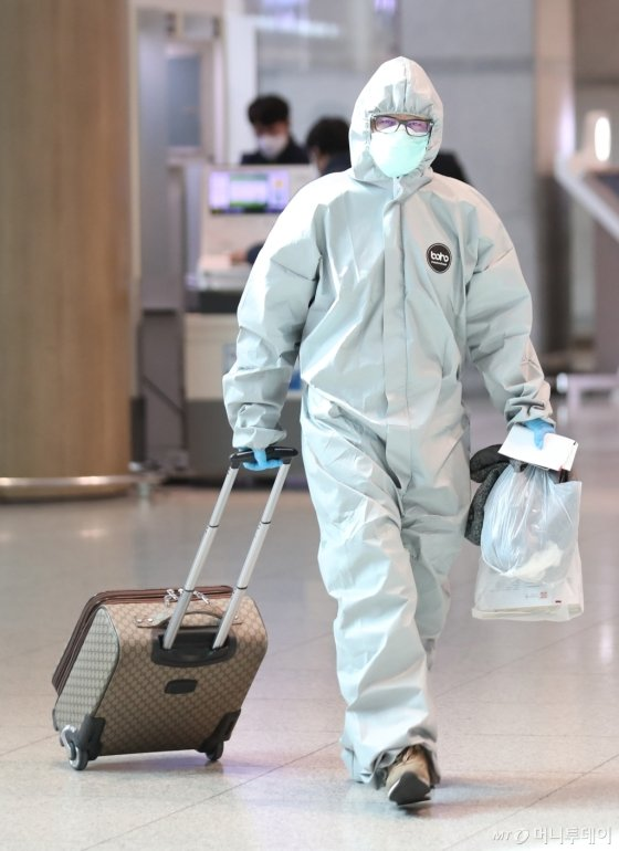 24일 오전 인천국제공항에서 심양발 비행기를 타고 온 한 입국자가 방진복을 입은 채 출국장을 나서고 있다. /인천공항=이기범 기자