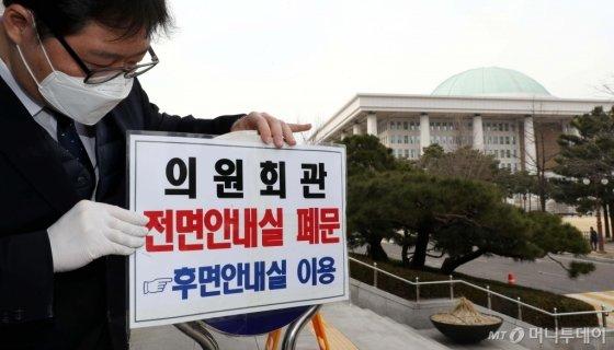 국회 관계자가 24일 오후 서울 여의도 국회 의원회관 2층 안내실 출입구 폐문을 알리는 안내문을 부착하고 있다. /홍봉진 기자