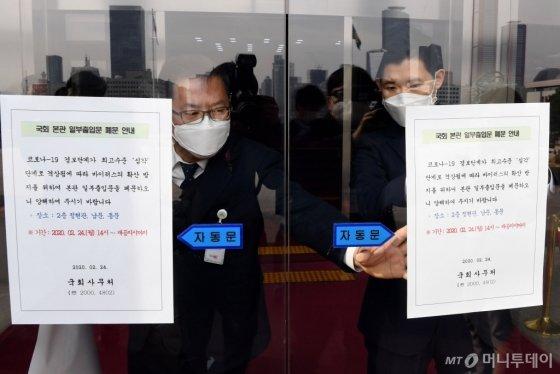 <br /> 19일 오후 서울 여의도 국회 정현관 출입문에 코로나19 바이러스 확산 방지를 위해 본관 일부 출입문을 페문한다는 안내문이 부착되어 있다. /홍봉진 기자