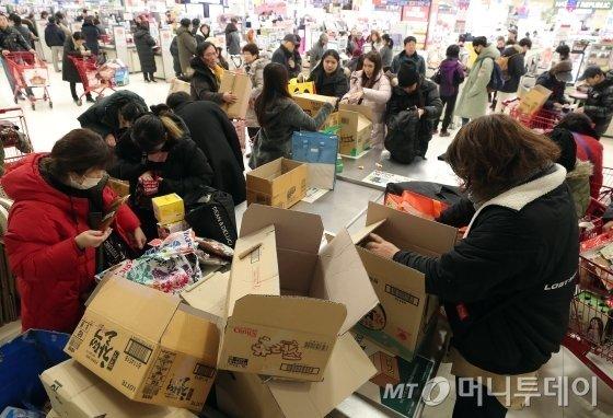 주요 대형마트 3사(이마트·롯데마트·홈플러스) 전 점포 자율 포장대에서 노끈과 테이프 제공이 중단된 지난해 4월 1일 오후 서울 시내의 한 대형마트를 찾은 시민들 및 관광객들이 직접 챙겨 온 장바구니와 박스를 접어 물건을 담고 있다./사진=김창현 기자 chmt@